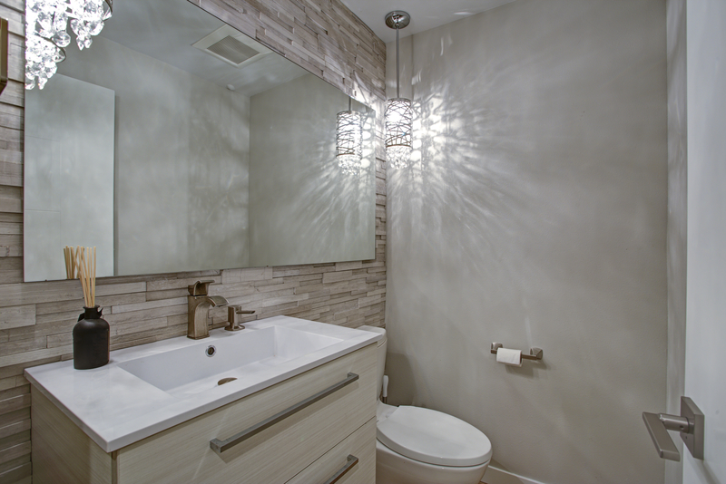 Contemporary bathroom design with taupe linear stacked tiles backsplash illuminated by decorative pendant.